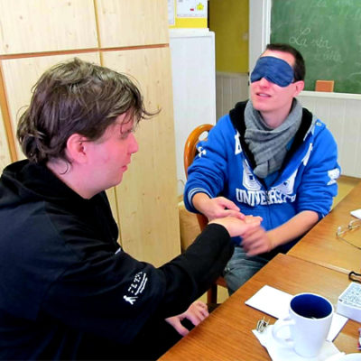 kép:MVGYOSZ munkatársa egy látóembert szemfedővel a szemén közösen érzékenyítő feladatot végeznek