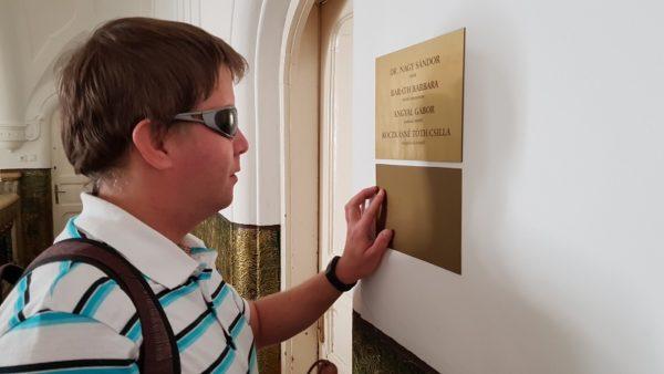 kép: ifjú látássérült férfi éppen egy brallie írásos táblát olvas