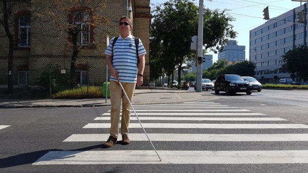 kép:ifjú látássérült férfi sétapálcával átkel a zebrán